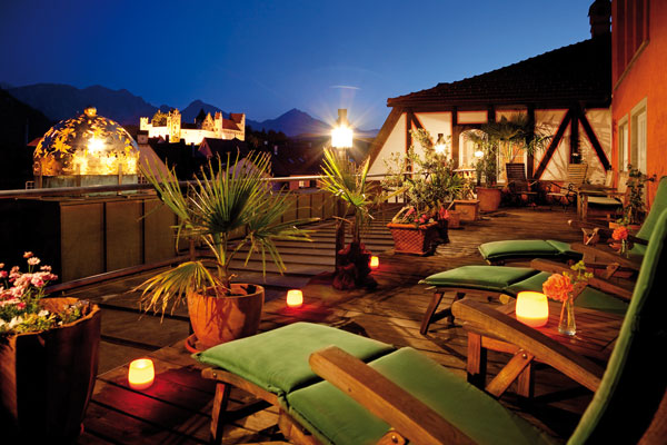 Romantic roof terrace at night with outlook to the illuminated 'Hohes Schloss' castle