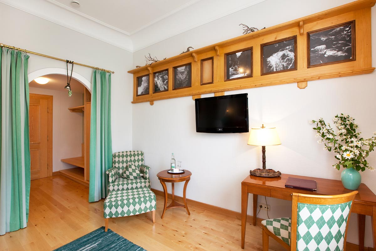 Double room of the Hirsch Hotel with armchair and seating